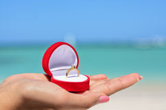 Female hand holding golden wedding ring in red jewellery box on Stock Photo