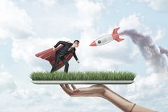 Female hand holding grass board with small businessman in red superman mask and cloak with silver red rocket on blue sky royalty free stock photography