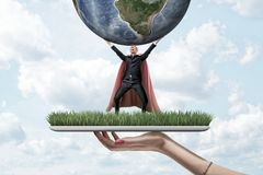 Female hand holding grass board with small businessman wearing red superman mask and cloak holding earth globe up on. Blue sky background. Success and strategy royalty free stock photography