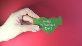 Female hand holding green paper heart with wings on red background - Happy Valentine`s Day stock video