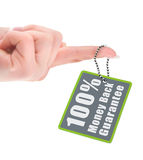 Female hand holding guarantee tag over white. Background Royalty Free Stock Images