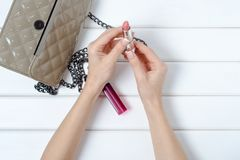 Female hand holding a handbag with lipstick Stock Photography