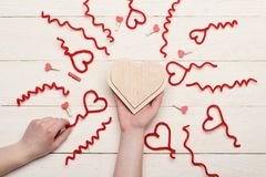Female hand holding handmade wooden heart, top view. Female hand holding handmade wooden heart. Red fuzzy wire hearts and tiny pegs on white vintage background stock image