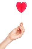 Female hand holding a heart-shaped lollipop.  stock photos