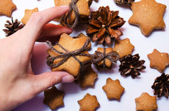 Female hand holding homemade rye cookies star shaped stack tied with brown rope on white background Royalty Free Stock Image