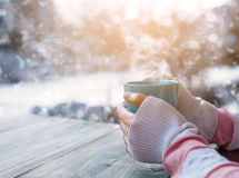 Female hand holding hot cup of coffee in winter Stock Images