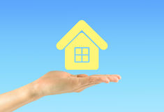 Female hand holding a house icon on a blue background Stock Image