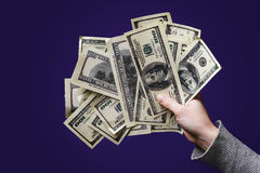 Female hand holding a hundred dollar bill on black background. c Royalty Free Stock Photography