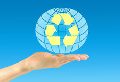 Female hand holding an icon of Earth and arrows renewal Royalty Free Stock Photos