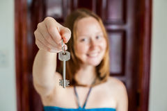 A female hand holding a key to the house on a background of a wooden door. Owning real estate concept Royalty Free Stock Photography