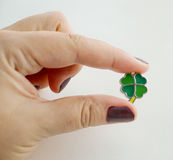 Female hand holding a leaf clover charm Royalty Free Stock Photo