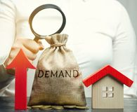 A female hand is holding a magnifying glass over a money bag with the word Demand, up arrow and a house. The concept of high royalty free stock photography