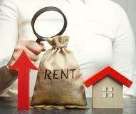 A female hand is holding a magnifying glass over a money bag with the word Rent, up arrow and a house. The concept of raising the stock photos