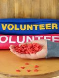 Female hand is holding many little hearts. Volunteer uniform in the background. Volunteering concept royalty free stock images