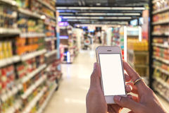 Female hand holding mobile smart phone on Supermarket blur backg Royalty Free Stock Photo