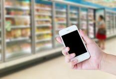 Female hand holding mobile smart phone on Supermarket royalty free stock photos