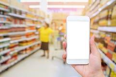 Female hand holding mobile smartphone over supermarket backgroun Royalty Free Stock Image
