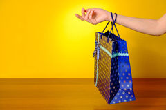 Female hand holding multicolor shopping bags on yellow background Stock Images