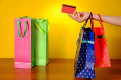 Female hand holding multicolor shopping bags on yellow backgroundFemale hand holding shopping bags and credit card on yellow backg Royalty Free Stock Image