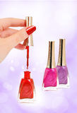 Female hand holding nail brush. Woman holding brush over opened bottle of red nail polish, two other bottles on the side Royalty Free Stock Photo