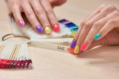 Female hand holding nails colors samples. Womans summer shellac nails. Choice summer fashion manicure Royalty Free Stock Image