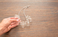 Female hand holding a necklace of glass on wooden background. Royalty Free Stock Images