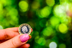 Female hand holding new british one sterling pound coin.  Royalty Free Stock Image