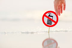 Female hand holding No phone calls sign on the beach. On sand background Stock Photo