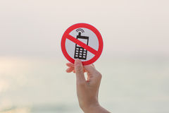 Female hand holding No phone calls sign on the beach. On sea background royalty free stock image