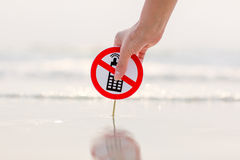 Female hand holding No phone calls sign on the beach. On sea background Royalty Free Stock Photography