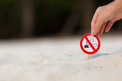 Female hand holding No smoking sign on the beach. On sand background royalty free stock images