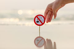 Female hand holding No smoking sign on the beach. On sea background stock photo
