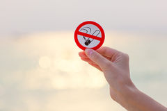 Female hand holding No smoking sign on the beach. On sea background royalty free stock image