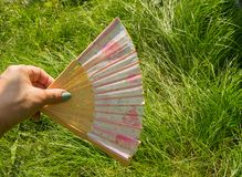 Female hand holding open a bamboo fan on a grass background, copy space royalty free stock images