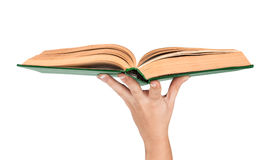Female hand holding an open vintage book in green cover. Concept Royalty Free Stock Image