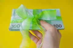 Female hand holding a pack of hundred euro banknotes with green bow-knot, gift or dividends concept, european union money. Female hand holding a pack of a stock photo