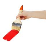 Female hand holding paint brush isolated on white background. Royalty Free Stock Image