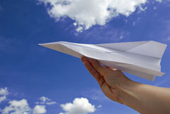 Female hand holding paper airplane Stock Image