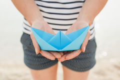 Female hand holding paper boat Stock Images