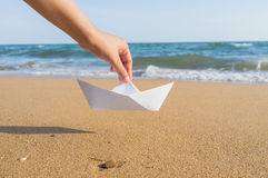 Female hand holding paper boat on the sea background Stock Image
