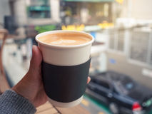 Female hand holding a paper cup of hot coffee, selective focus. Royalty Free Stock Photos