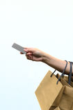 Female hand holding paper shopping bag and pay by credit card Stock Photography