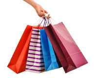 Female hand holding paper shopping bags isolated on white Royalty Free Stock Photos