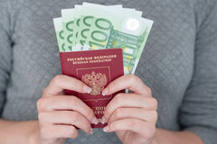 Female hand holding a passport with Euro banknotes. Royalty Free Stock Photography