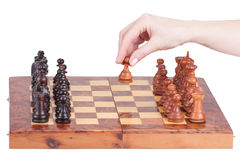 Female hand holding a pawn on the chessboard Stock Photography