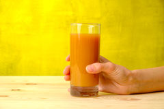 Female hand is holding peach juice in the glass Royalty Free Stock Photography