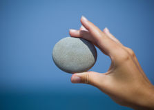 Female hand holding pebble against sea Stock Photo