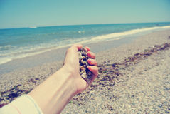 Female hand holding pebbles on the beach, retro/vintage stock images