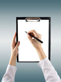 A female hand holding a pen and clipboard with blank paper (docu. Ment, report) on blurred background. Top view Royalty Free Stock Photos