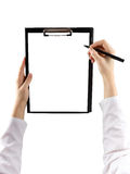 Female hand holding a pen and clipboard with blank paper (docume. Nt, report) isolated on white background. Top view Stock Images